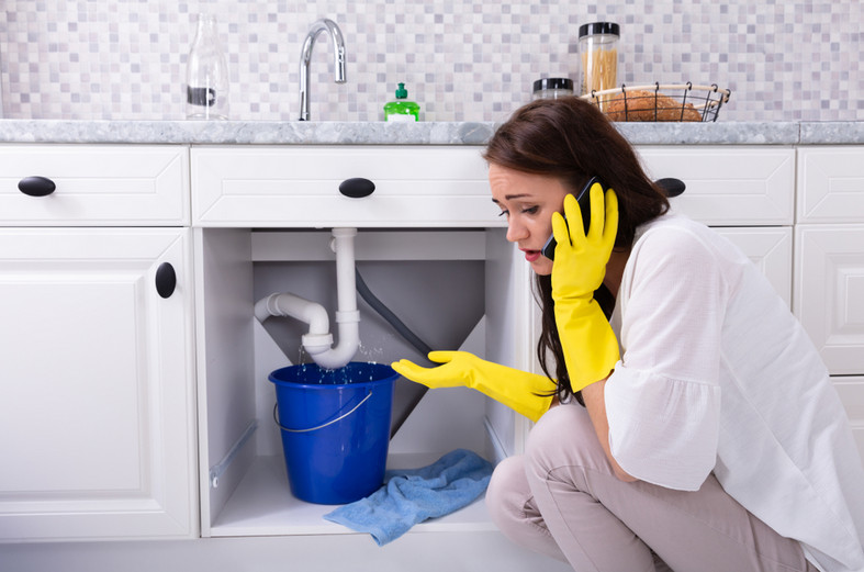 woman calling an emergency plumber in sydney for fix her leaking sink trap